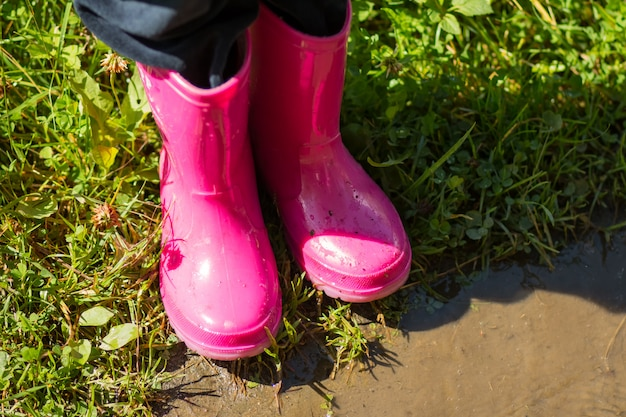 Child wearing red pink rain boots, jumping into a puddle. kids bright red rubber boots, gardening, boots. rainy day fashion.garden rainy rubber shoes. boots for rainy day. autumn kids boots concept.