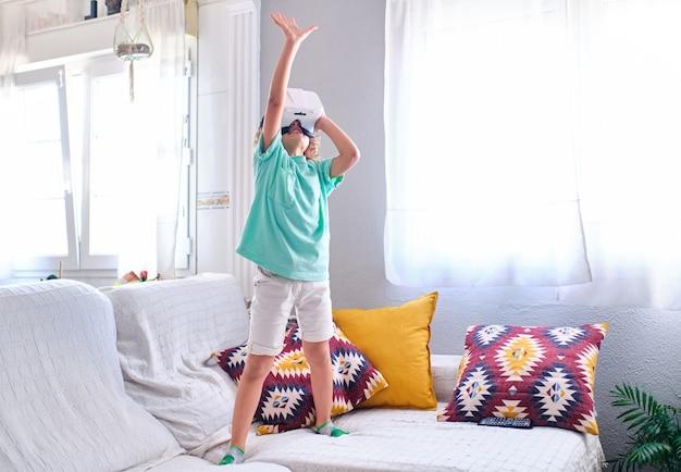 バーチャルリアリティゴーグルを身に着けている子供が手を上げる
