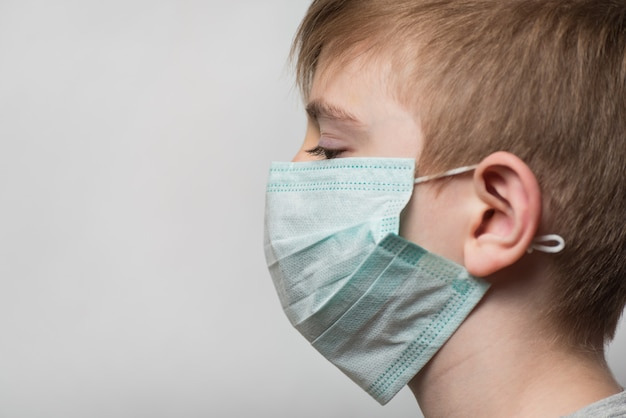 子供は細菌から保護するために医療用マスクを着用しています。ポートレートサイドビュー。