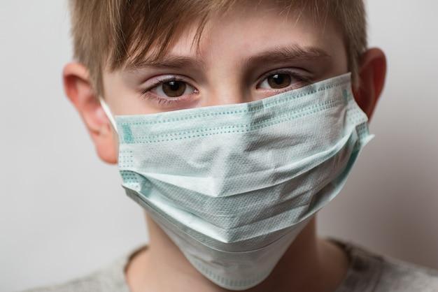 子供は彼をコロナウイルスから保護するために保護用の医療用マスクを着用しています。彼の顔に医療用マスクを持つ少年。