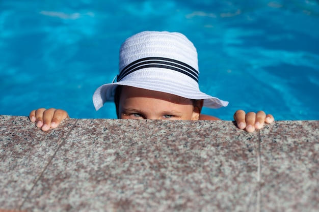 Child in white panama hat plays in pool happy charming girl in white straw hat decorated with ribbon...