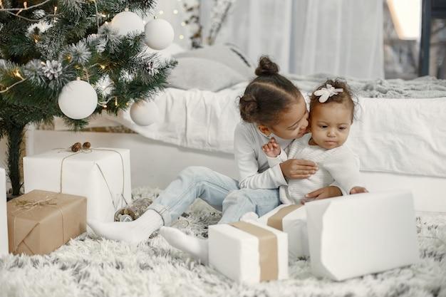 Bambino in un maglione bianco. figlie stitting vicino all'albero di natale. due sorelle a casa.