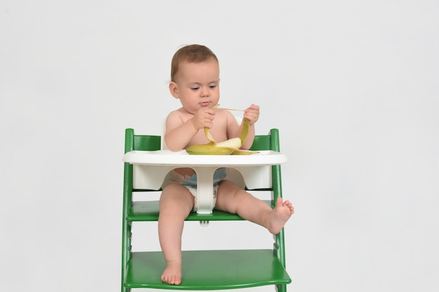 Child who is playing while eating in a highchair on white background