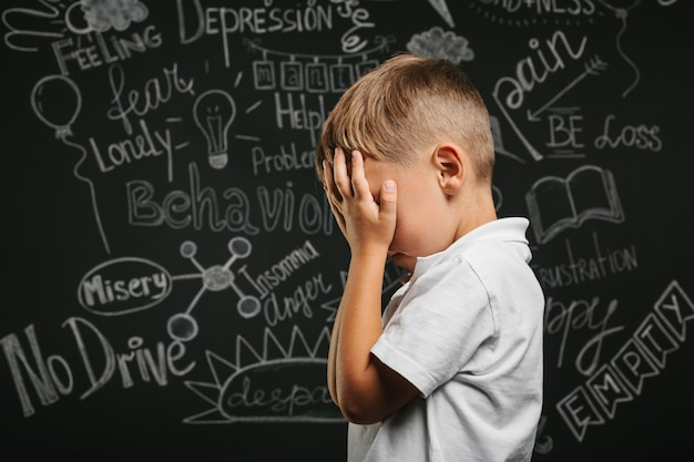 うつ病が両手を閉じた状態で黒い黒板にいる子供