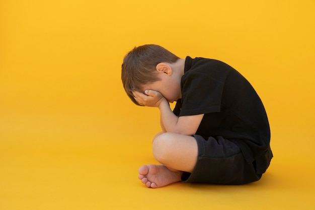 Child whose depression is sitting on the color floor