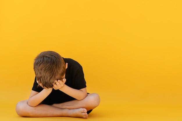 Ребенок, чья депрессия сидит на цветном полу