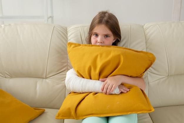 Ребенок с гипсовой повязкой на сломанном запястье или руке сидит на диване, концепция выздоровления и болезни
