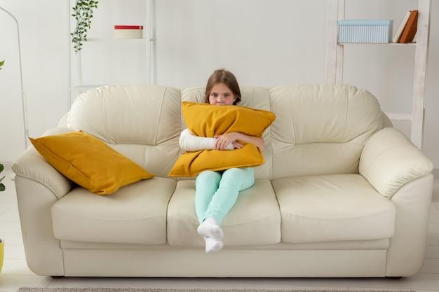 부러진 손목이나 팔에 캐스트가 소파 회복 및 질병 개념에 앉아있는 아이