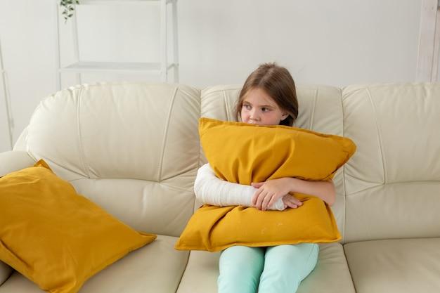 부러진 손목이나 팔에 깁스를 한 아이는 소파에 앉아