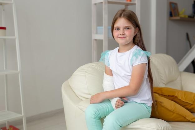 Ребенок с гипсовой повязкой на сломанном запястье или руке улыбается и веселится на диване. положительный настрой
