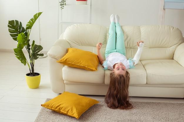 Ребенок с гипсовой повязкой на сломанном запястье или руке улыбается и веселится на диване позитивно