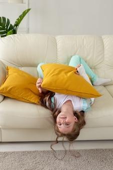 Ребенок с гипсовой повязкой на сломанном запястье или руке улыбается и веселится на диване