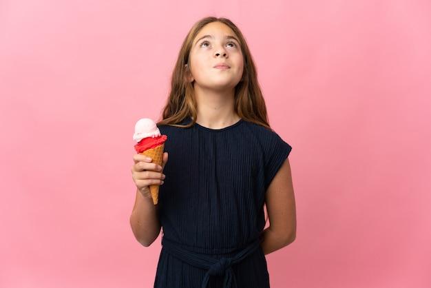Ребенок с мороженым корнет над изолированным розовым и смотрит вверх