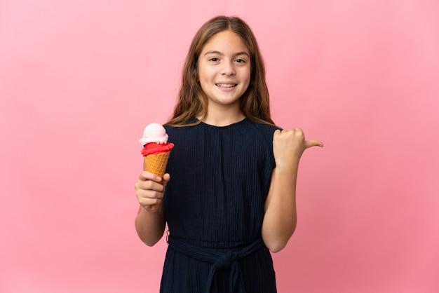 Ребенок с мороженым корнет на изолированном розовом фоне, указывая в сторону, чтобы представить продукт