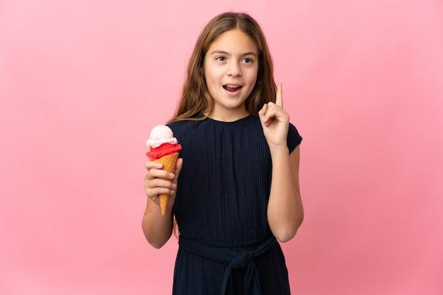 손가락을 가리키는 아이디어를 생각하는 고립 된 분홍색 배경 위에 코넷 아이스크림을 가진 아이