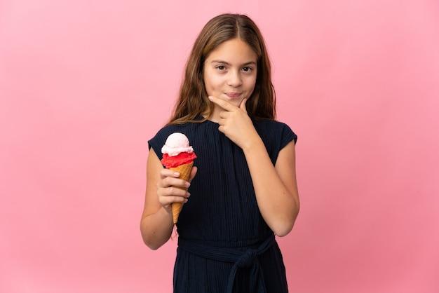 Ребенок с мороженым корнет над изолированным розовым мышлением
