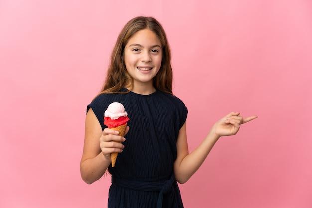 横に指を指している孤立したピンクの壁の上にコルネットアイスクリームを持つ子供