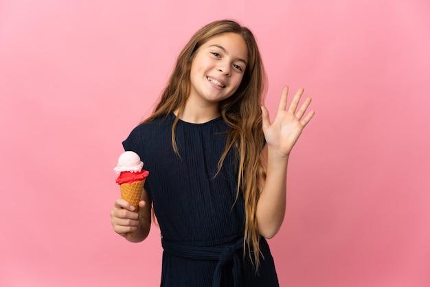 Ребенок с мороженым корнет над изолированной розовой стеной салютует рукой со счастливым выражением лица