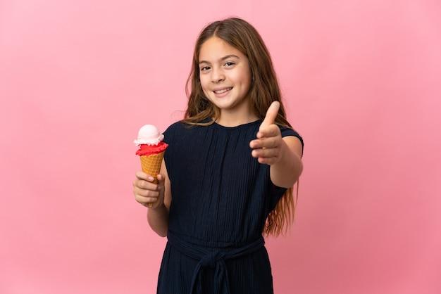 좋은 거래를 닫기 위해 악수하는 고립 된 분홍색 벽 위에 코넷 아이스크림을 가진 아이
