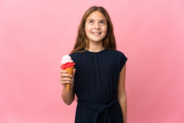 Ребенок с мороженым корнет над изолированной розовой стеной, думая об идее, глядя вверх