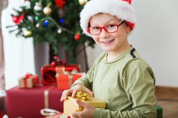 Ребенок с золотым подарком и шляпу санта