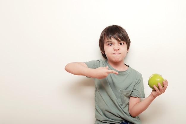 しかめっ面の子供は、白い背景の上にもう一方の手で持っている青リンゴを指しています