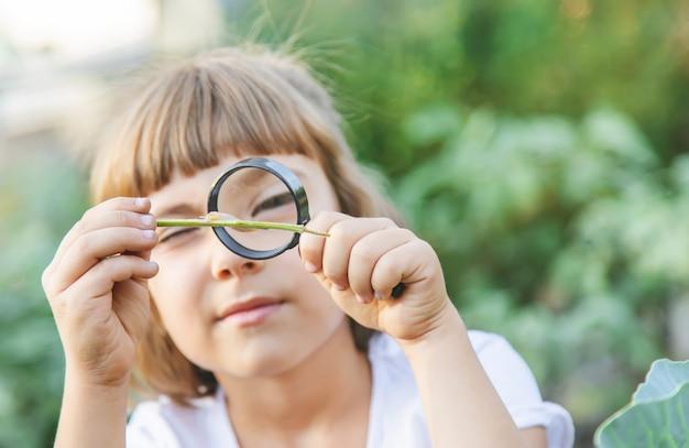 Ребенок с увеличительным стеклом в руках.