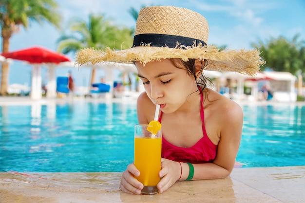 プールサイドでカクテルを飲む麦わら帽子を持つ子供
