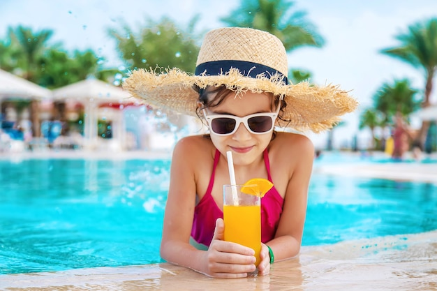 Ребенок в соломенной шляпе пьет коктейль у бассейна