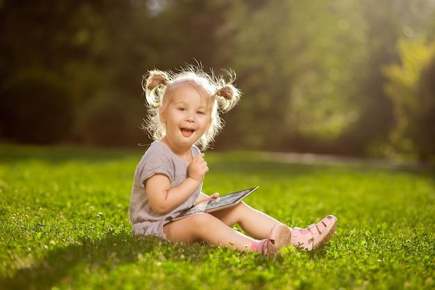 公園に座っているタブレットを持つ子供