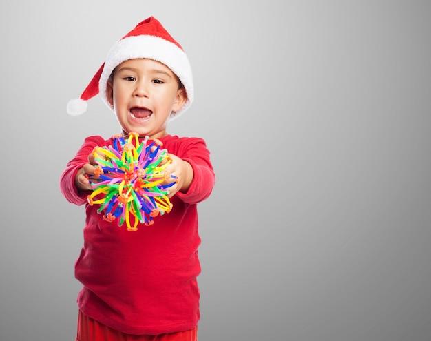 おもちゃとサンタの帽子を持つ子供