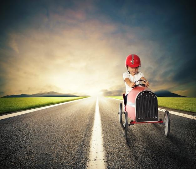 Ребенок с игрушечной машинкой едет по проселочной дороге