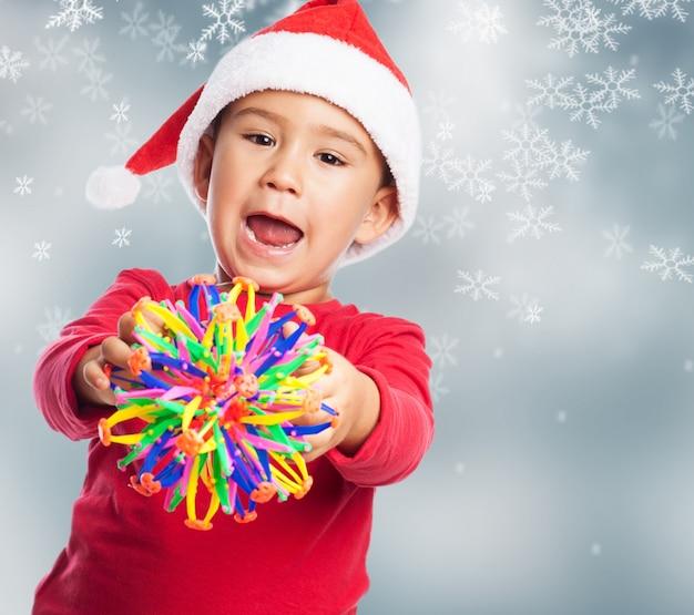 Ребенок с игрушкой с фоном снежинки