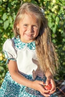庭にリンゴを持った子供。セレクティブフォーカス。自然。
