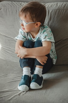 Child with autism in glasses sits on the sofa and sad