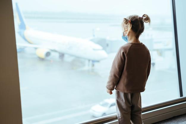 공항 창 너머로 보이는 배낭을 메고 있는 아이