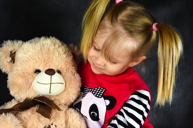 A child with a balloon hugs a toy of a teddy bear and is sad and happy