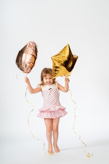 Child with balloons in the shape of a heart and a star
