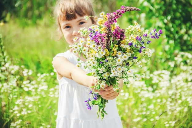 Child with a bouquet of wildflowers. selective focus. nature.