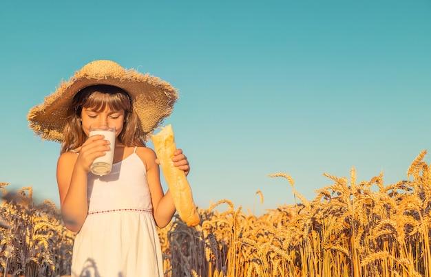 Ребенок с хлебом и молоком в пшеничном поле