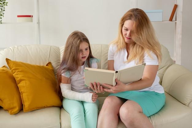 腕と石膏が折れた子供は、母親と一緒に家で過ごします。子供の病気、前向きな見通しと回復。