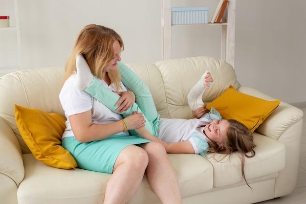腕と石膏が壊れた子供は、母親の子供時代の病気と一緒に家で過ごす