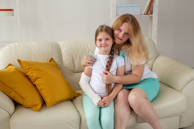 Child with broken arm and gypsum spend time at home with mother. childhood illnesses, a positive