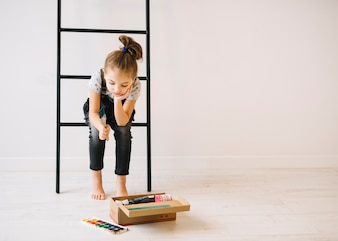 Child with brush sitting on ladder near wall and box with colors on floor