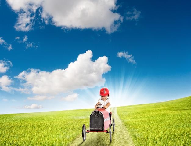 Ребенок с автомобилем играет на проселочной дороге