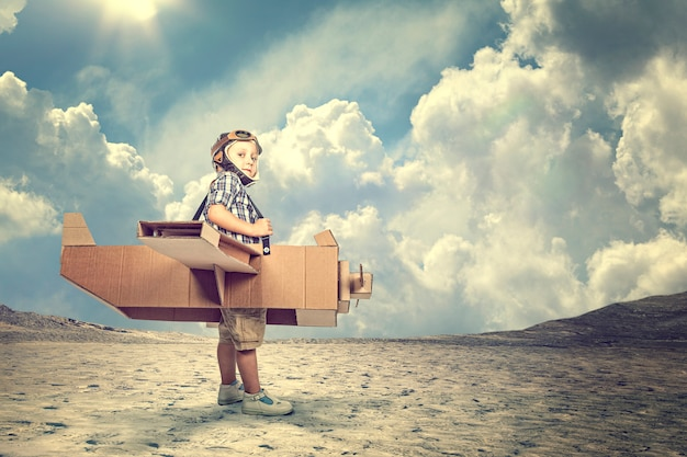 Child with cardboard airplane in a desert