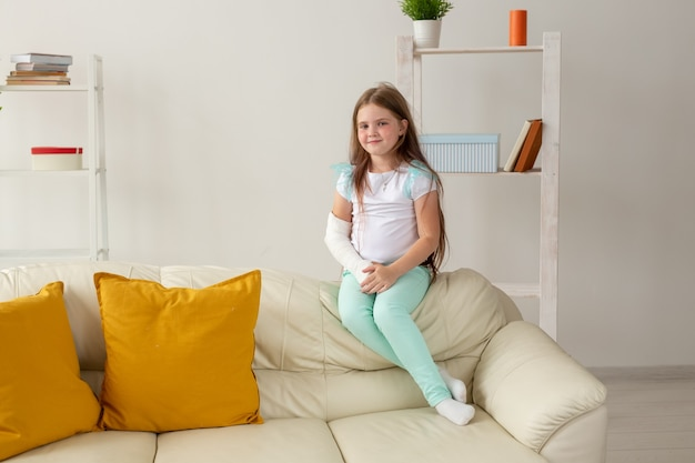 Child with a cast on a broken wrist or arm smiling and having fun on a couch. positive attitude