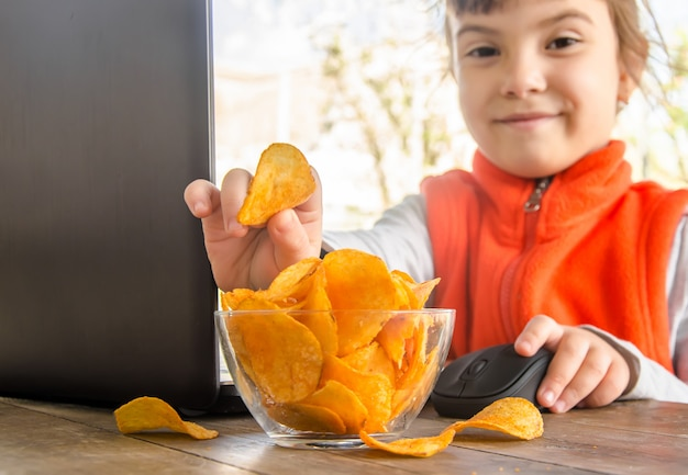 Child with chips behind a computer