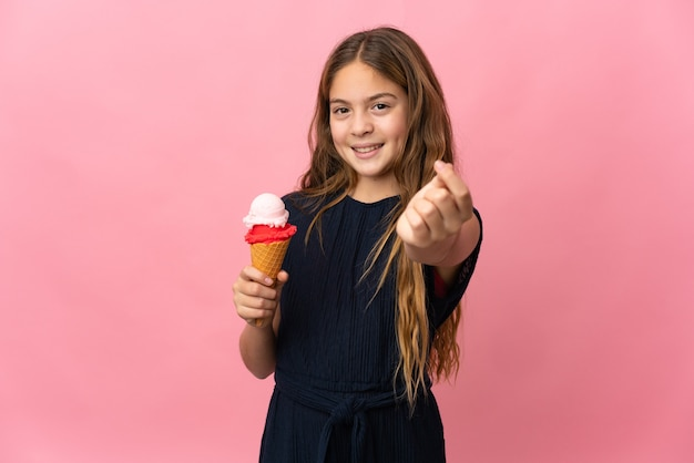 Child with a cornet ice cream over isolated pink background making money gesture