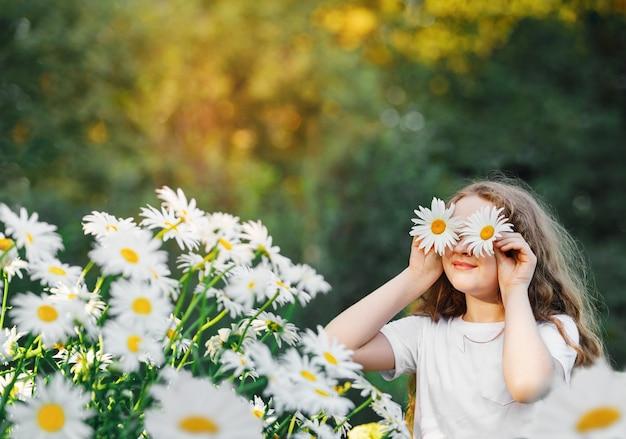 Ребенок с глазами ромашки на зеленом фоне в летнем парке